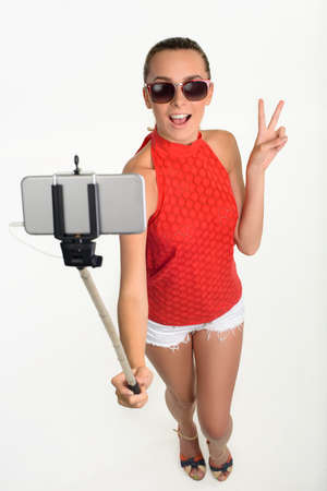 teeny: Girl showing piece sign taking selfie. Young lady showing piece sign with two fingers. Teeny holding selfie stick on white background. Stock Photo
