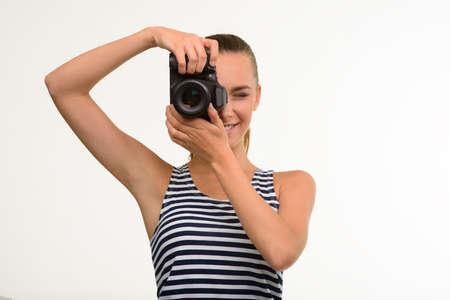 Pretty girl making photo. Nice girl with camera. Paparazzi making photo using professional camera. Stock Photo