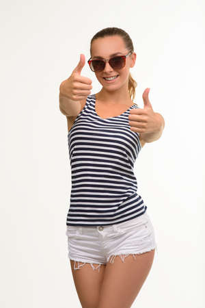 thumbsup: Pretty exited girl giving thumbs-up. Sexy woman in sunglasses. Nice student posing on white background.