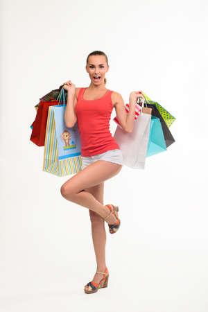 joyfull: Young woman holding shopping bags. Fashion shopping girl. Full length portrait of shopping teenager.