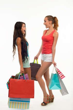 playmates: Dos estudiantes de compras. amigas felices con bolsas de compras en el fondo blanco. descuentos de temporada.