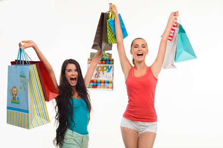 playmates: Two excited girls with shopping bags. Friends go shopping. Shopping time with friends. Stock Photo