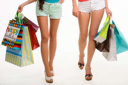 go to the shopping: Elegant legs of girls walking with shopping bags. Two girls go shopping. Shopping time with friends. Stock Photo