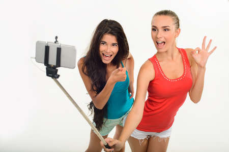 playmates: Pretty young girls making selfie. Friends taking picture of themselves. Students with monopod on white background.