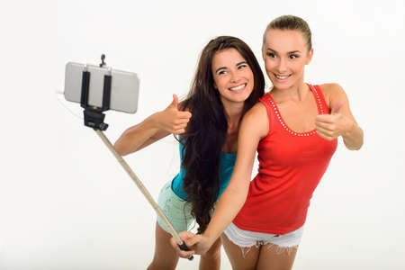 playmates: Pretty young girl-friends making selfie with fingers-up. Friends taking picture of themselves. Girls with monopod.
