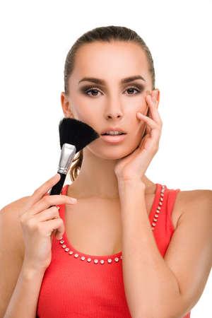 blusher: Make-up artist applying blusher. Pretty woman holding blush brush. Beautiful girls face close-up.