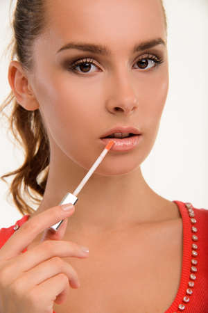 lipgloss: Visagiste paints lips with lipgloss. Sensual woman applying gloss on her lips. Close-up of girls juicy lips. Stock Photo