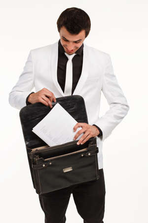 careerist: Clerk putting documennts in briefcase. Successful office worker. Young employee with briefcase on white background.