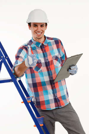 hand job: Handyman stood by ladder giving thumbs-up. Engineer with clipboard on white background. Happy builder with pleased smile.