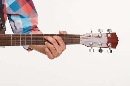 fingerboard: Fingerboard of guitar and hand playing guitar. Mans hand holding fingerboard. Picture of fingerboard on white background.