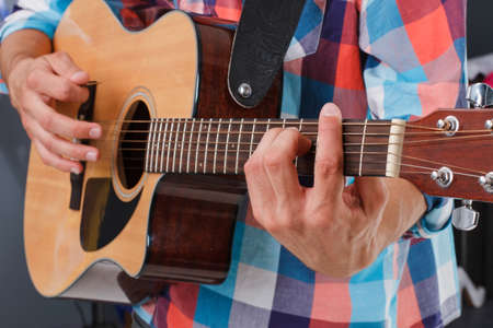 fingerboard: Acoustic guitar being played. Fingers holding fingerboard. Mans hand holding fingerboard.