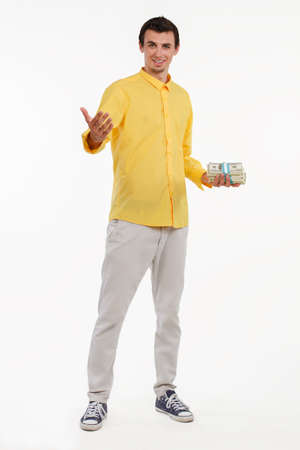 Executive holding piles of cash. Young smash director holding money. Millionaire making inviting gesture.