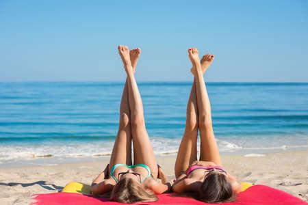 Le ragazze che prendono il sole sul mare. Fidanzate hanno un periodo di riposo sulla spiaggia. Lunghe gambe di giovani ragazze sulla spiaggia. Relax in vacanza. ragazze sessuali che si trovano in riva al mare.