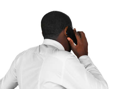 negotiating: Composed conversation. Black man on the phone. Executive is negotiating. Afroamerican answering cellphone.