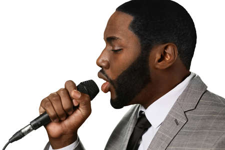 vocalist: Darkskinned man sings jazz. Great jazz voice. Professional vocalist perfroming. Elegant black singer on stage. Stock Photo