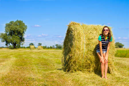 minx: Minx girl is standing near haystack and laughing on the sunny field.