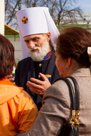 priest's ritual robes: The orthodox priest is speaking to two women in christian holiday near church. They are listening to him with interest. Editorial