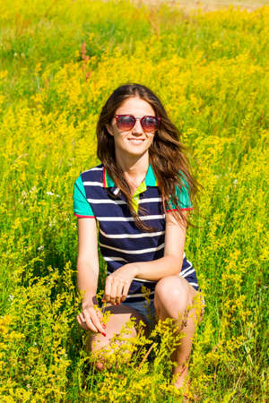 Beautiful girl is sitting in tall grass and yellow flowers and beautiful girl is sitting in tall grass and yellow flowers and smiling stock photo mightylinksfo