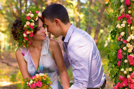 beautiful rose: Beautiful couple is sitting in sunny park. They are looking at each other with passion and gonna kiss. Stock Photo