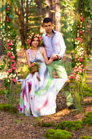 fiance: Beautiful woman in wreath of roses and long dress is sitting on flower swing in sunny park with bouquet flowers in her hand. Her fiance is standing near her and holding her hand.