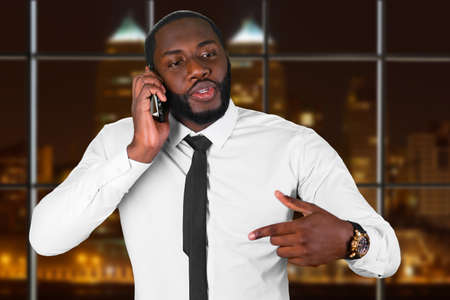 night shift: Convincing talk on the phone. Night shift in call center. Black man having business conversation. Company headquarters at night.