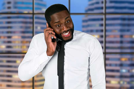 megalopolis: Surprised man on the phone. Evening phone call. Black man having business conversation. Headquarters in megalopolis. Stock Photo