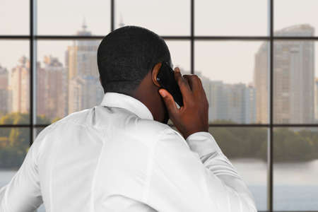 composed: Composed phone conversation. Phonetalk next to a window. Executive is negotiating. Daytime negotiation in the city. Stock Photo