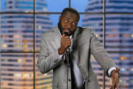 Black stand-up comedian. Avond comedy show op televisie. Comedian op stedelijke achtergrond. Moppen te vertellen op het podium. Stockfoto