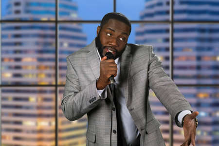 Black stand-up comedian. Evening comedy show on television. Comedian on urban background. Telling jokes on stage.