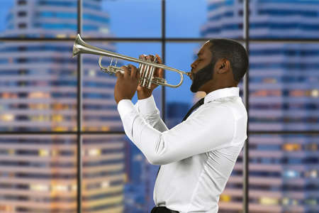 megalopolis: Enthusiast with a trumpet. Jazz performance in megalopolis. Impressive musician has skills. The view from studio window.