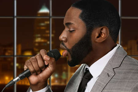 jazz singer: Darkskinned man sings jazz. Singer on urban background. Professional vocalist perfroming. Nighttime in concert hall.