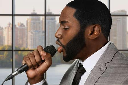 concert hall: Darkskinned man sings blues. Daytime at vocal studio. Concert hall in elite district. Elegant afro singer on stage. Stock Photo