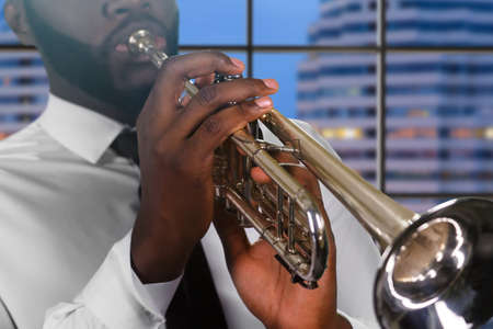 trumpet player: Concentrated trumpet player. Trumpet player on city background. Precision of trumpet player. Evening trumpet improvisation. Stock Photo
