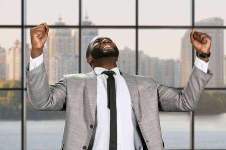 achievment: The businessmans victory. Happy manager in the office. Black man celebrating sucess. Business success in the capital.