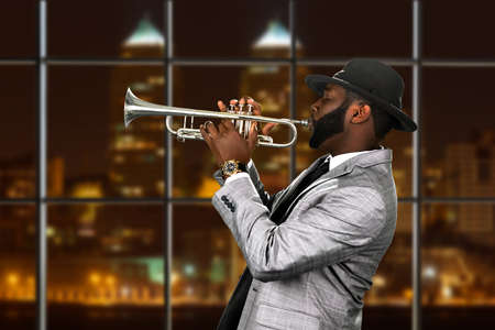 trumpet player: Afro trumpeters performance at night. Musician in city concert hall. Gifted trumpet player. Stylish musician with a trumpet. Stock Photo