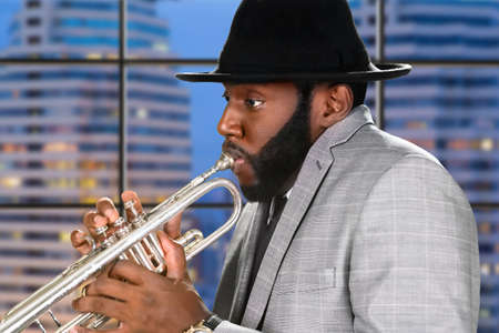 skillful: Evening performance of skillful trumpeter. Darkskinned trumpeter on city background. Classy trumpeter performing. Dont distract the trumpeter.