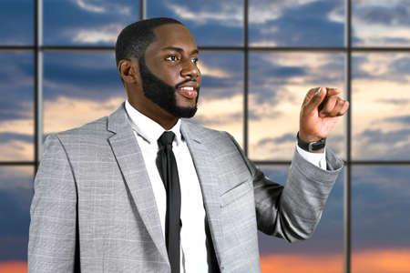Responsable africain souriant au bureau. Homme d'affaires satisfait des résultats. L'homme d'affaires noir est occupé. Vous cherchez une solution.