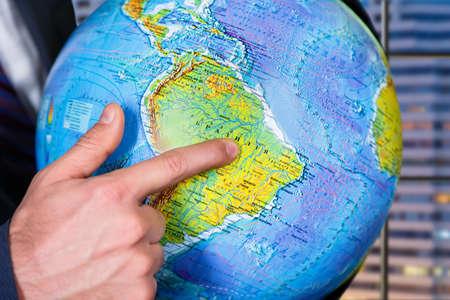 explores: Businessman explores globe in office.