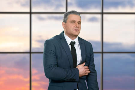 medical attention: Businessmans heart pain during sunset. Man heavily stressed at workplace. Ease the heartache. Chief needs medical attention. Stock Photo
