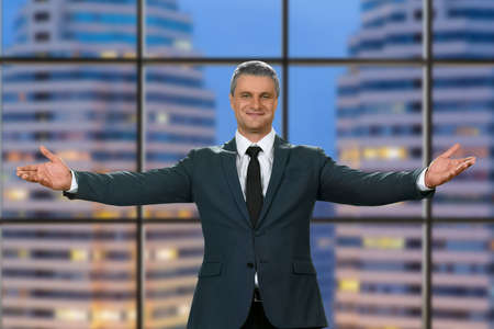 polite: Adult businessman welcomes office visitors. Evening speech of polite topmanager. Friendly atmosphere in business center. Its all for you. Stock Photo