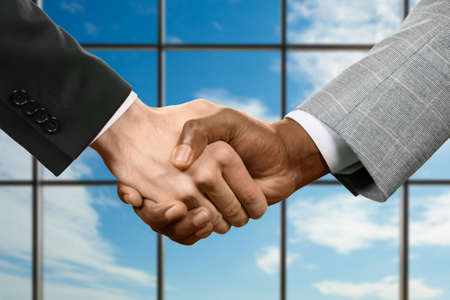 realtionship: Businessmen shake hands in office.