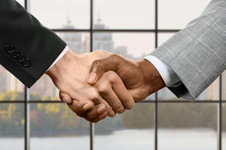 Les hommes d'affaires se serrent la main au quartier général. Poignée de main d'affaires sur le fond de la ville. Les négociations de jour ont été couronnées de succès. Au nom du progrès.