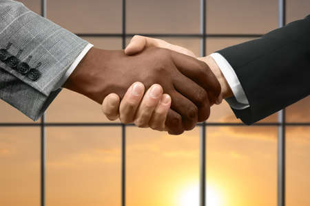 realtionship: Business handshake on sunset background. Men shake hands beside window. Together we win. Equality and tolerance.