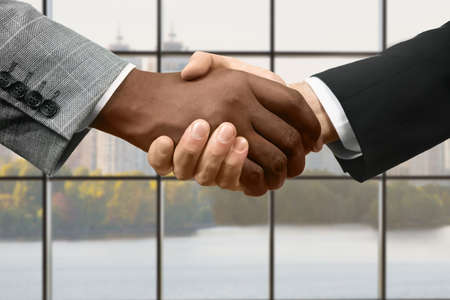 realtionship: Managers shake hands in office.