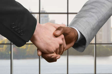 realtionship: Business handshake on city background.