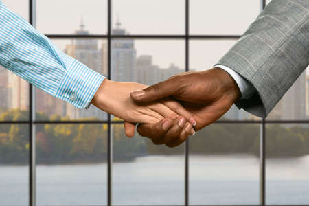 realtionship: Businessman and woman office handshake.