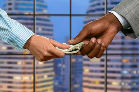 megalopolis: Megalopolis business couple passing money.
