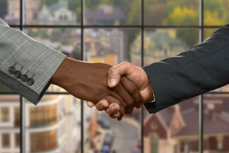 realtionship: Midday handshake of two businessman.