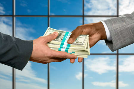 gaining: Businessman repays debts at daytime. Men pass dollars beside window. Gaining a significant percent. Good month for a salesman.