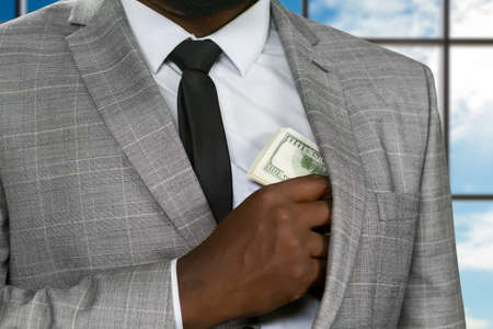 safer: Afroamerican office manager hides money. Black office worker hiding cash. Feed the greed. Its safer to hide.